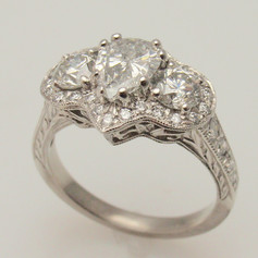 three primary diamonds in halo and platinum mounting
