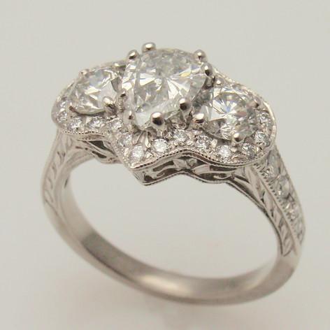 three primary diamonds in halo and platinum mounting