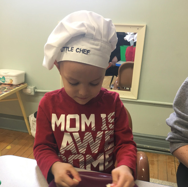 boy with chef hat pulling apart bread