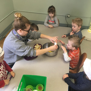 educator helping a child break an egg into a bowl at a table full of children
