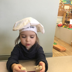 girl wearing a chef hat pulling apart br