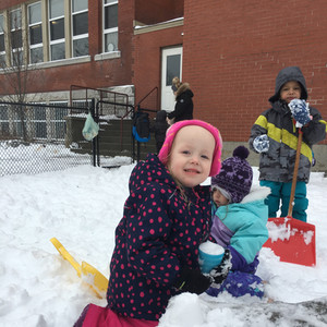 girl smiling while playing in the snow.J