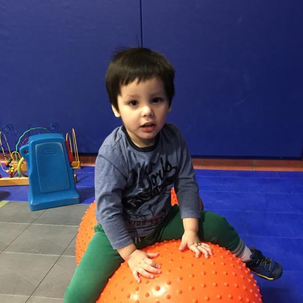 boy riding a large orange ball