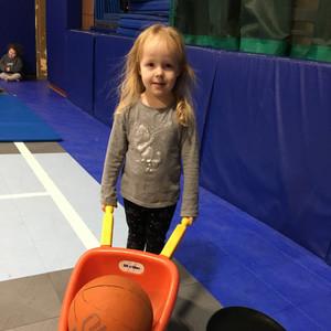 Girl pushing ball in an orange wheelbarrow