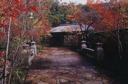 雲仙旅亭半水廬/紅葉に包まれた柿葺き門と車廻りへの石橋