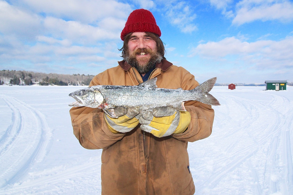 man with frozen fish ice fishing wi