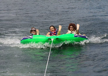 women tubing on lake