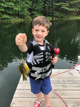 little boy with fish on pier