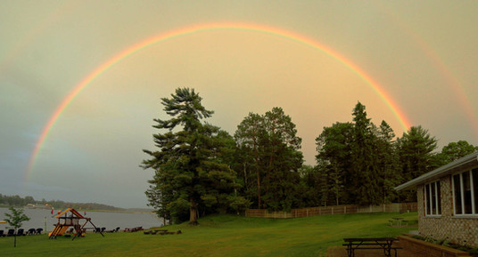 rainbow behind cabin at resort