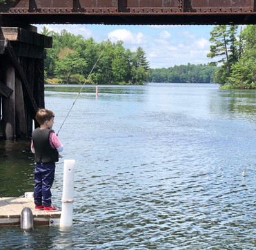 boy fishes off dock at northern wisconsin resort