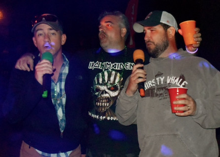 3 men doing karaoke at resort