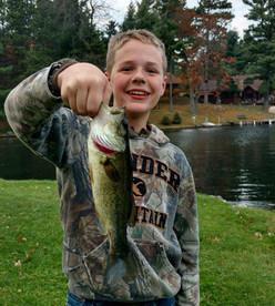 boy holds caught fish at lake resort