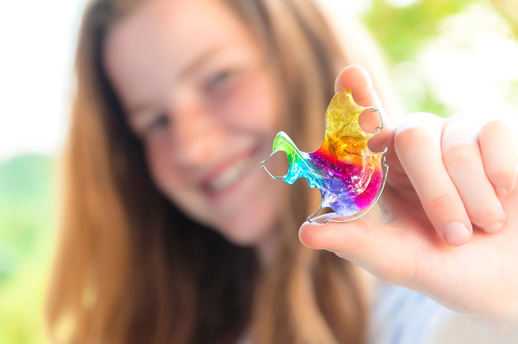 Girl holding rainbow coloured orthodonti