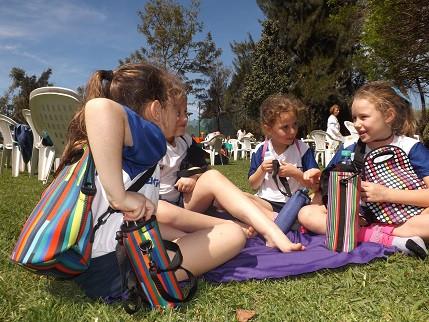 chicas comiendo en el parque con vianderas neoprene