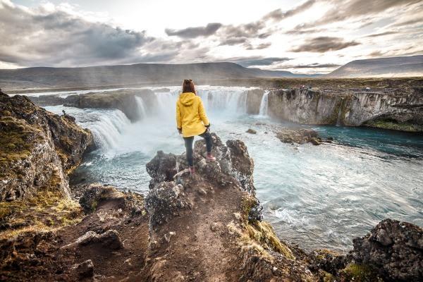 Turista contemplando una cascada islandesa - Diesel vs Gasolina : ¿Cuál es la mejor opción para tu viaje en Islandia?