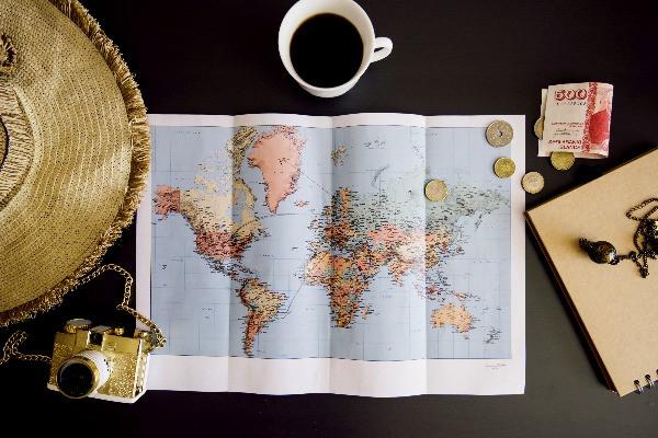 Vista panorámica de un mapamundi con monedas y billetes islandeses, cámara de fotos y taza de café - La moneda de Islandia - Guía de conversión para el viajero