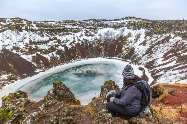 Mujer observando el impresionante cráter de uno de los volcanes en Islandia