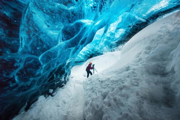 Turista escalando una cueva de hielo - La cueva de hielo Lofthellir en Islandia