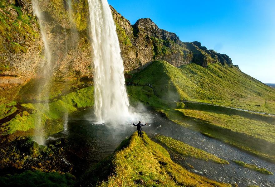 Turista contemplando la cascada Selialandsfoss - La cascada de Selialandsfoss en Islandia
