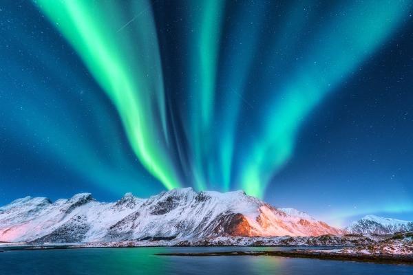 Volcán nevado islandés con auroras boreales verdes en el cielo - Islandia y las Auroras Boreales: Todo lo que debes saber