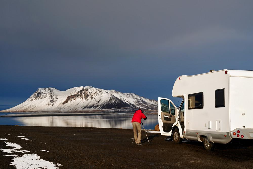 Turista en autocaravana fotografiando un volcán nevado - Una de las mejores formas de acampar en Islandia