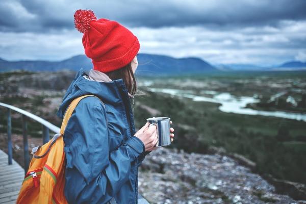 Joven turista bien abrigada con gorro gorro y chaqueta impermeable en Islandia
