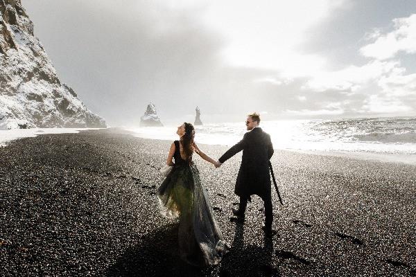 Pareja andando por las playas negras de Vík - Luna de miel en Islandia