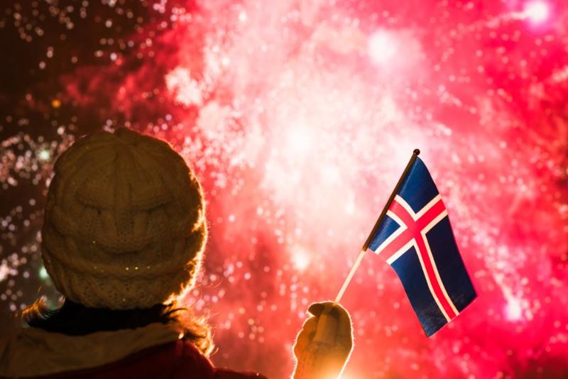 Turista sujetando una bandera islandesa mientras observa fuegos artificiales - Año Nuevo en Islandia 2021