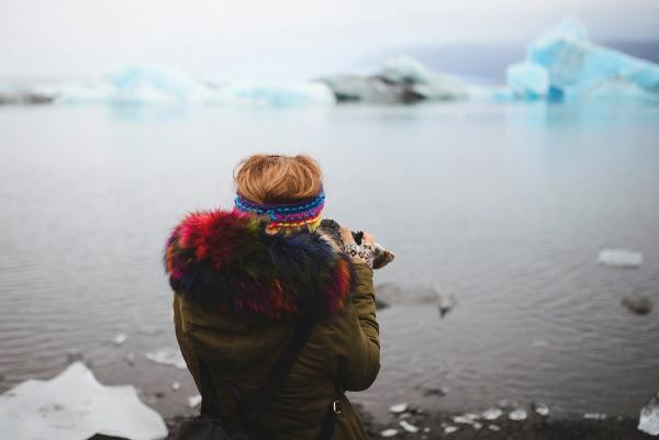 Turista con parka tomando foto a un icerberg - Guía de Viaje a Islandia en camper