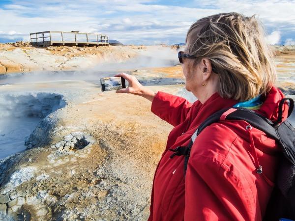 Turista senior tomando fotos a un geysir en Islandia - ¿Es necesario comprar una tarjeta SIM de Islandia?