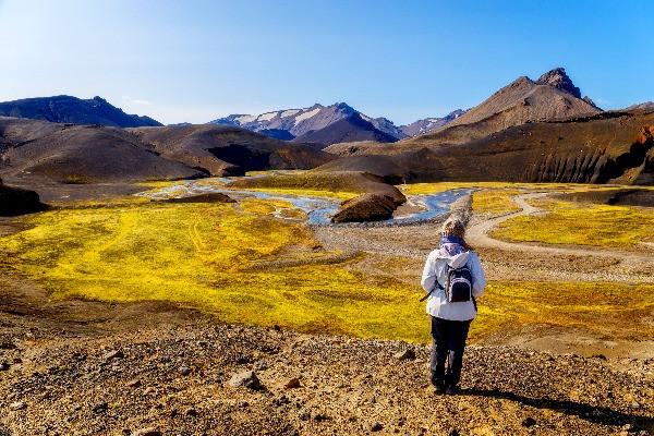Turista contemplando los paisajes de la ruta F208 - Carretera de montaña en Islandia