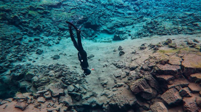 Turista con traje de neopreno buceando en Islandia - Snorkel en Islandia: Buceando en la Fisura de Silfra