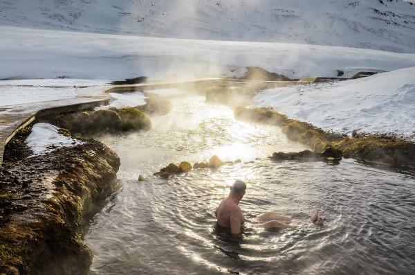 Turista bañándose en las aguas termales de Reykjadalur – Senderismo y baño en Islandia