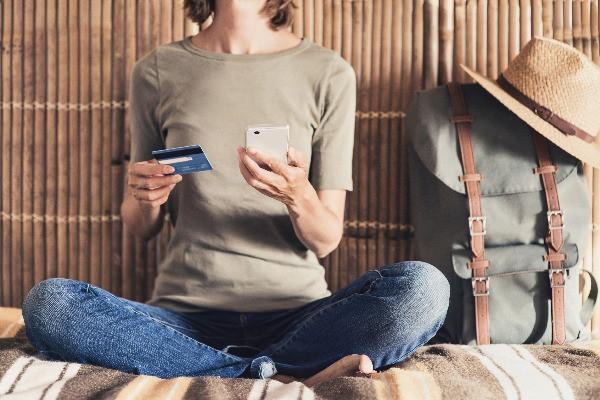 Turista haciendo una reserva con tarjeta de crédito
