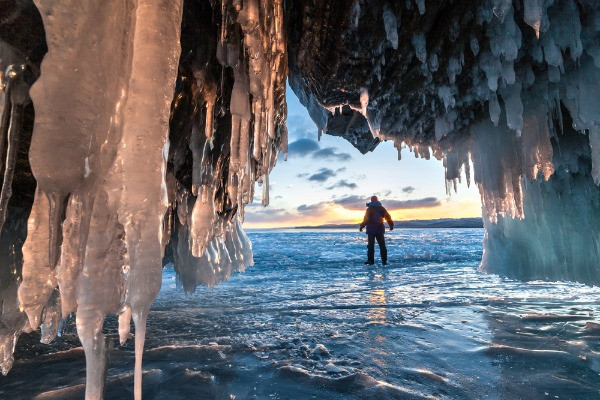 Turista contemplando el paisaje a la entrada de una cueva de hielo con estalagmitas - La cueva de hielo Lofthellir en Islandia