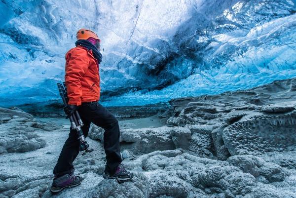Turista equipado con ropa de invierno, casco, botas y trípode dentro de una cueva de hielo - La cueva de hielo Lofthellir en Islandia