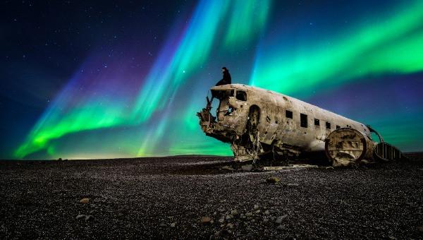 Turista contemplando una aurora boreal sobre los restos de un avión abandonado - Islandia y las Auroras Boreales: Todo lo que debes saber