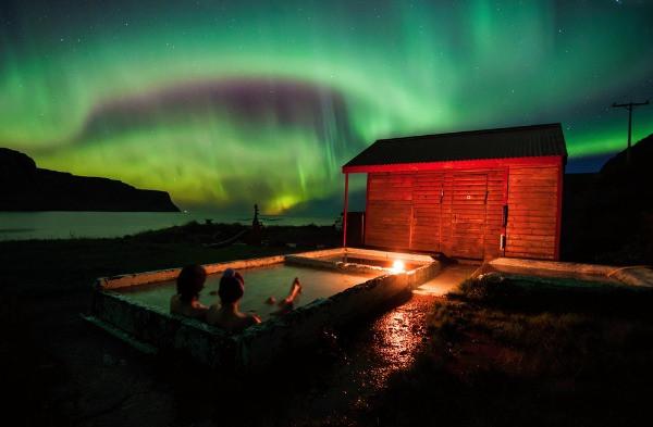 Vista panorámica a la Aurora Boreal mientras una pareja se baña en jacuzzi termal - Uno de los mejores planes para hacer en Islandia