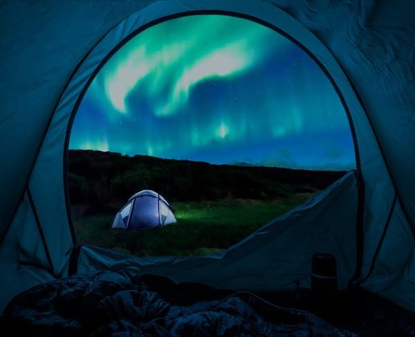Turista contemplando las auroras boreales desde su tienda de campaña - Islandia y las Auroras Boreales: Todo lo que debes saber