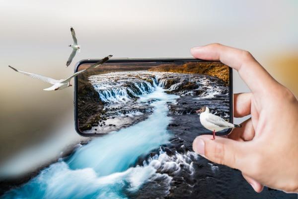 Turista contemplando los paisajes islandeses a través de un teléfono móvil - ¿Es necesario comprar una tarjeta SIM de Islandia?