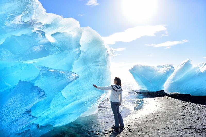 Turista tocando un iceberg gigante - Qué ver en Islandia: Recorrido en Autocaravana