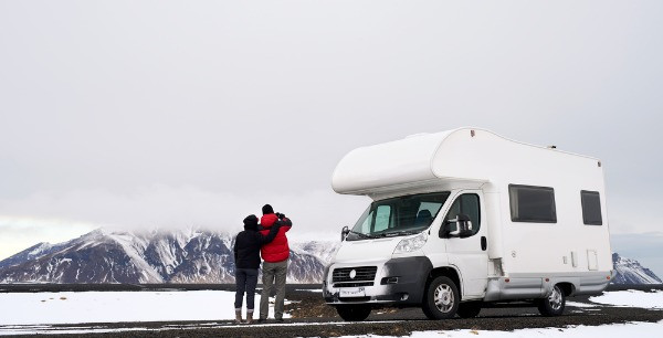 Turistas junto a una autocaravana en una carretera nevada de Islandia - Guía para conducir en Islandia en Marzo