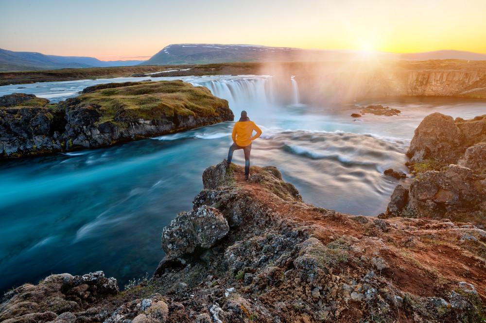 Turista contemplando desde lo alto la Cascada Godafoss - Guía actualizada de turismo de Islandia: ¿Qué ver y hacer?