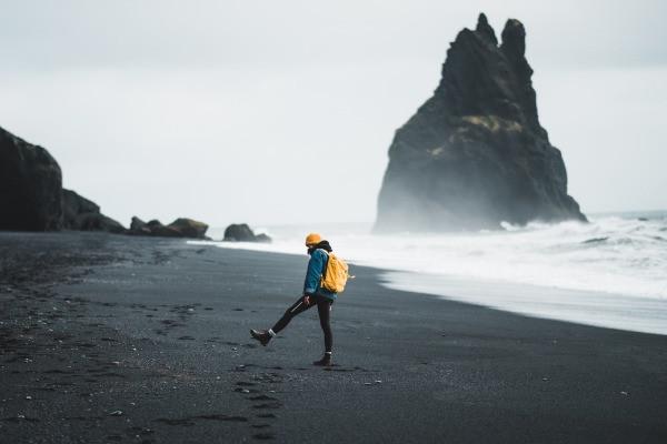 Turista caminando por Vík atracción turística de Islandia