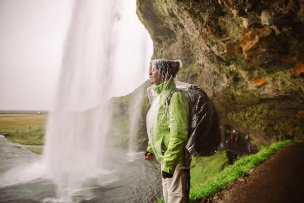 Turista contemplando una cascada y protegida por un chubasquero - Guía de Viaje a Islandia en camper