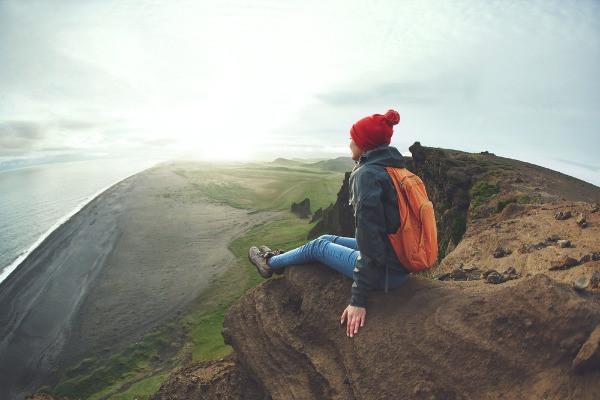 Turista contemplando Islandia desde una roca - Guía de Viaje a Islandia en camper