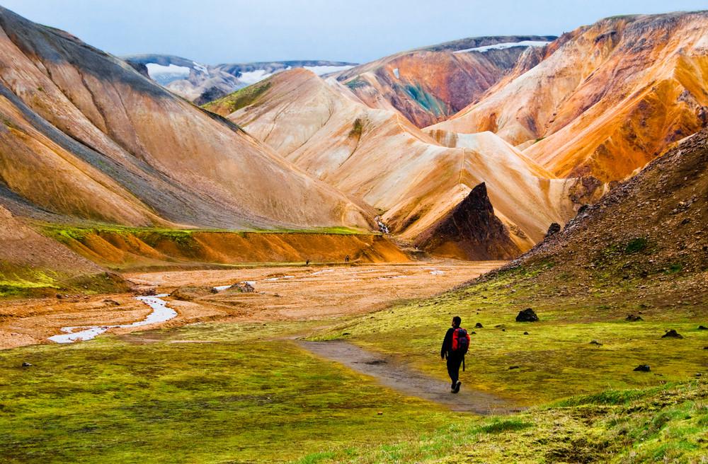 Turista haciendo senderismo por las montañas de Landmannalaugar - Guía actualizada de turismo de Islandia: ¿Qué ver y hacer?