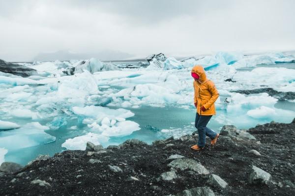 Turista caminando cerca de icebergs - El tiempo en Islandia por mes y estación del año