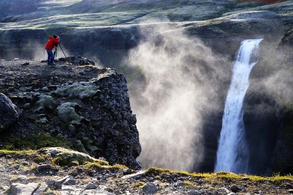 Turista fotografiando la cascada Haifoss - La hipnotizante cascada de las tierras altas de Islandia