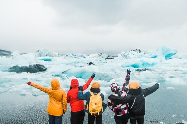 Grupo de turistas contemplando un glaciar abrigadas con chaquetas impermeables - Cómo vestirse en Islandia